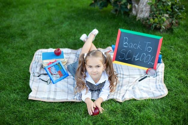 Studentessa sorridente sveglia che si siede sull'erba con pranzo, libri vicino alla scuola. di nuovo a scuola. concetto di educazione. educazione prescolare. copia spazio. bambina a pranzo e impara su un prato nel parco.
