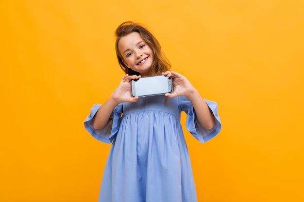 Cute teen sorridente in un abito blu mostra il telefono in posizione orizzontale con un modello su uno sfondo giallo
