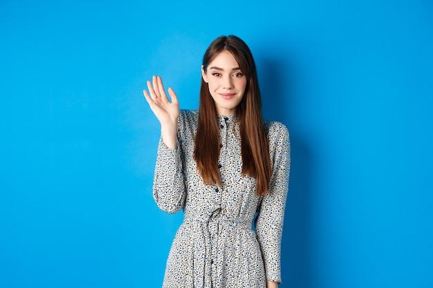 Donna sorridente carina agitando la mano per salutarti, salutandoti con un sorriso timido, in piedi in abito contro il blu. Foto Premium