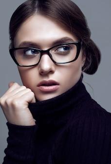 Ragazza sveglia dello studente che indossa maglione dolcevita nero e gli occhiali alla moda