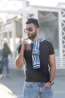 Hipster maschio giovane arabo elegante sveglio con i baffi e la barba e con gli occhiali bere succo di frutta