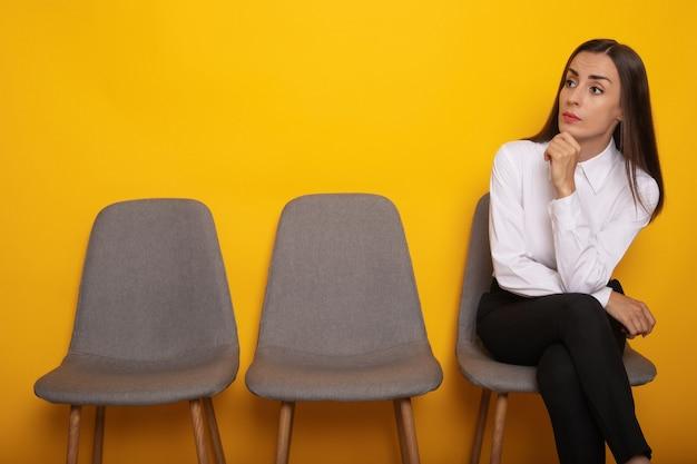 Una bella donna bruna moderna ed elegante è seduta sulla linea delle sedie all'appuntamento per il colloquio di lavoro