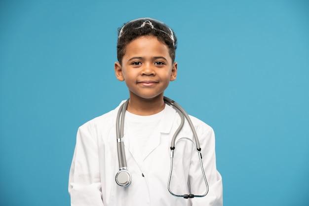 Ragazzino sveglio di successo di etnia africana in whitecoat con occhiali protettivi medici sulla testa e stetoscopio sul collo