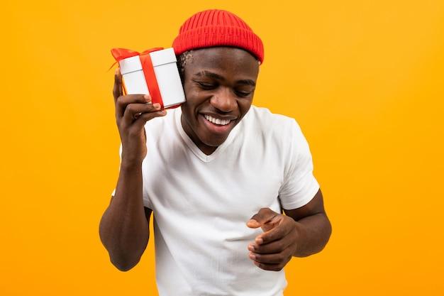 L'uomo nero africano sorpreso sveglio con un sorriso in una maglietta bianca tiene un contenitore di regalo con un nastro rosso per il suo giallo di compleanno