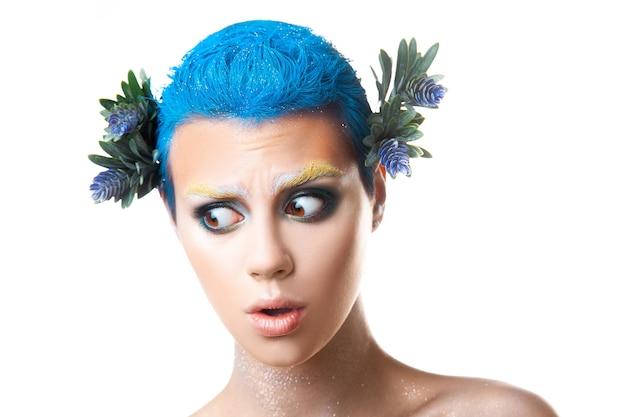 Ragazza carina sorpresa con trucco multicolore e acconciatura blu corta studio girato isolato