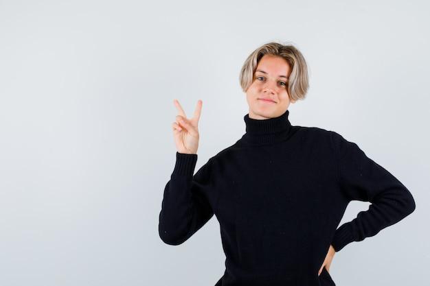 Ragazzo adolescente carino in maglione a collo alto nero che mostra gesto di pace e sembra allegro, vista frontale.
