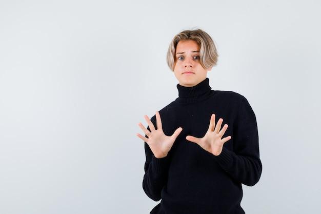 Ragazzo adolescente carino in maglione a collo alto nero che mostra gesto di resa e sembra spaventato, vista frontale.