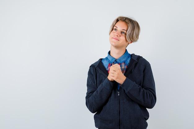 Ragazzo teenager sveglio che stringe le mani nel gesto di preghiera in camicia, felpa con cappuccio e guardando speranzoso, vista frontale.