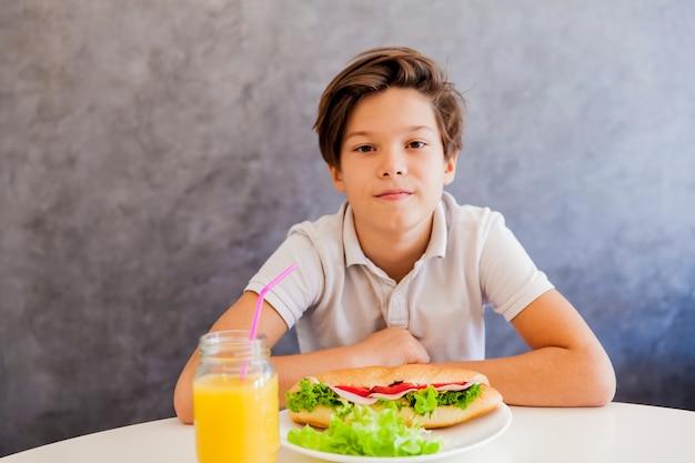 Ragazzo teenager sveglio che mangia prima colazione sana a casa