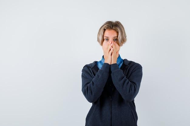 Ragazzo teenager sveglio che tiene le mani sulla bocca in felpa con cappuccio e sembra spaventato. vista frontale.