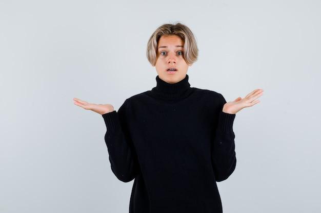 Ragazzo adolescente carino che mostra un gesto impotente in un maglione a collo alto nero e sembra perplesso, vista frontale.