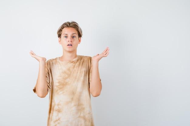 Ragazzo adolescente carino che mostra gesto impotente in maglietta e sembra sconcertato. vista frontale.