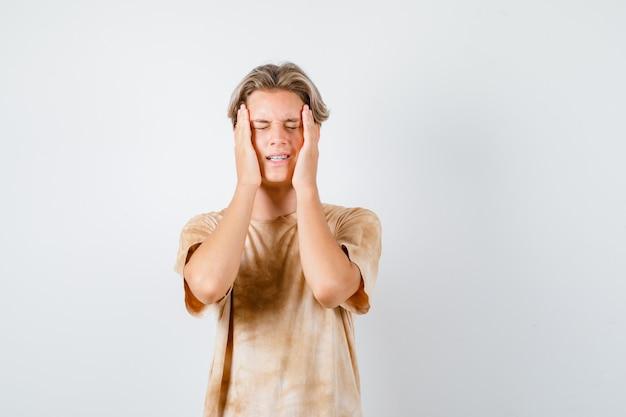 Ragazzo adolescente carino in maglietta che tiene le mani sulla testa e sembra irritato, vista frontale.