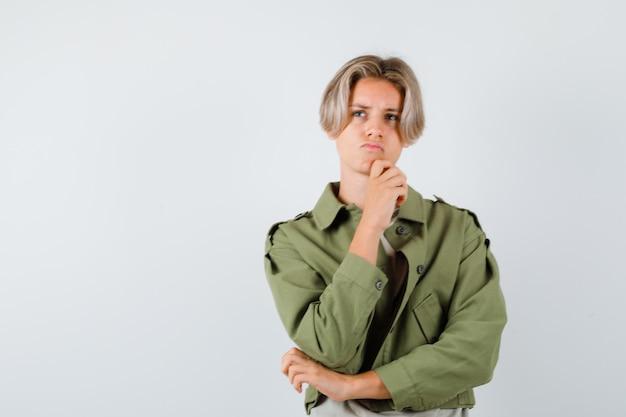 Ragazzo teenager sveglio con la mano sul mento, distogliendo lo sguardo in giacca verde e guardando pensieroso, vista frontale.