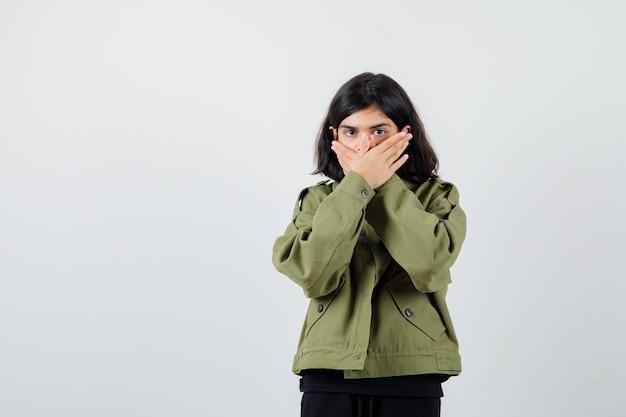 Ragazza teenager sveglia che tiene le mani sulla bocca in giacca verde militare e sembra spaventata, vista frontale.