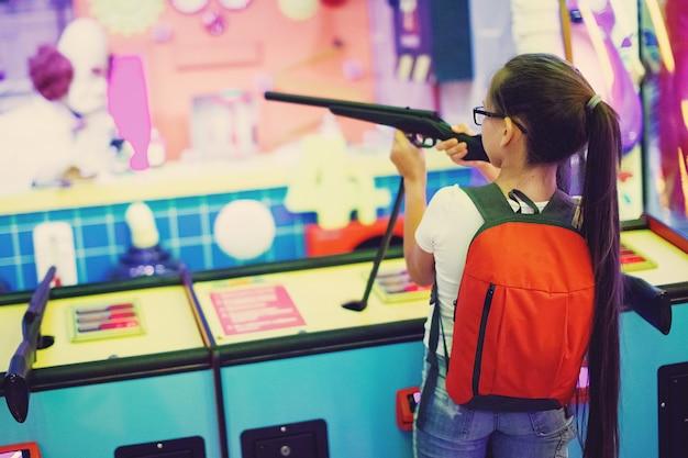 Cute teen girl gioca un fucile spara arcade in macchina da gioco in un parco di divertimenti.