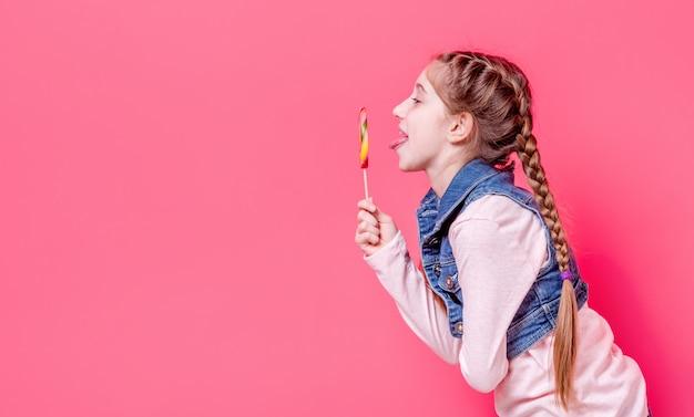 Ragazza teenager sveglia con la lecca-lecca della caramella