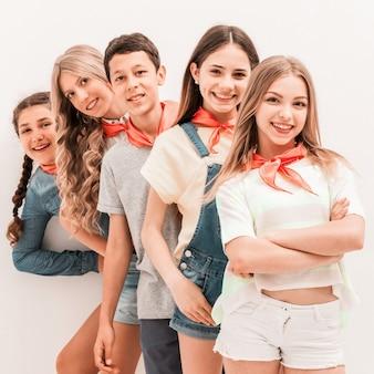 Bambini adolescenti carini in piedi uno per uno
