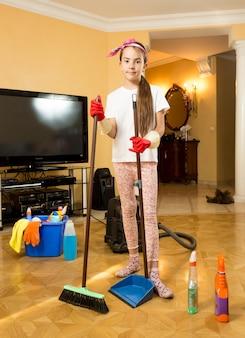 Adolescente carino che pulisce il pavimento in legno con spazzola e paletta