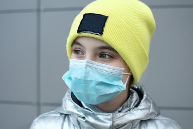 Carina ragazza adolescente in maschera medica sul viso contro sars-cov-2 all'aperto su edificio grigio