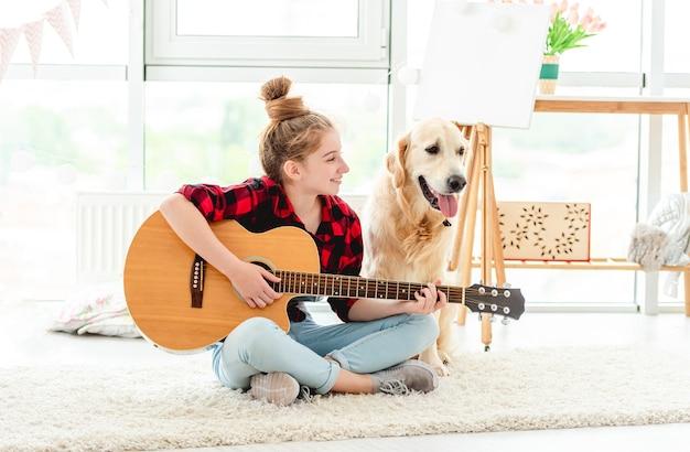 Carina ragazza adolescente a suonare la chitarra con bel cane al chiuso