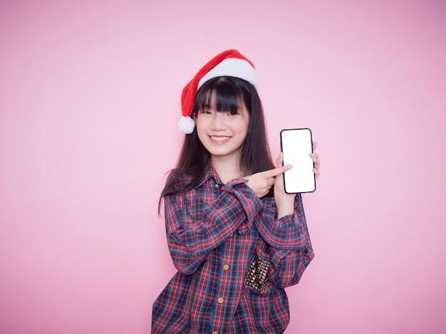 Ragazza adolescente carina in cappello della santa che tiene smartphone con lo schermo in bianco sulla parete rosa. spazio per il testo