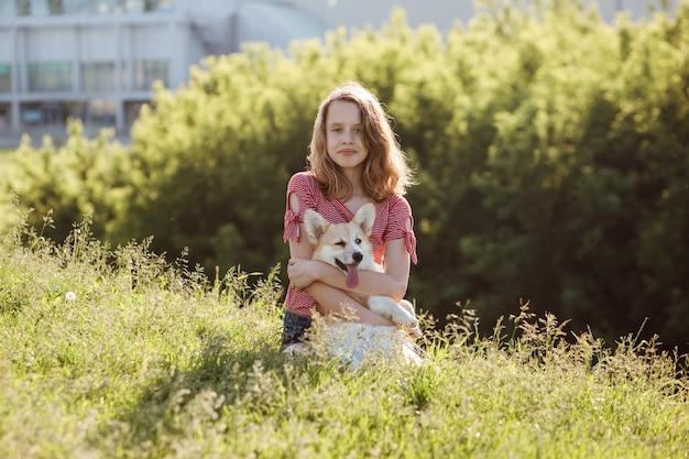 La ragazza sveglia dell'adolescente abbraccia il cane di pembroke del corgi gallese all'aperto nel parco della città in estate.