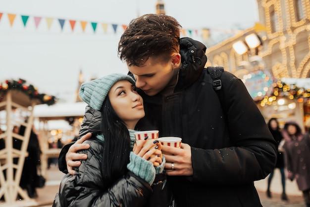 Coppia tenera carina trascorre del tempo insieme al mercatino di natale e bere caffè caldo