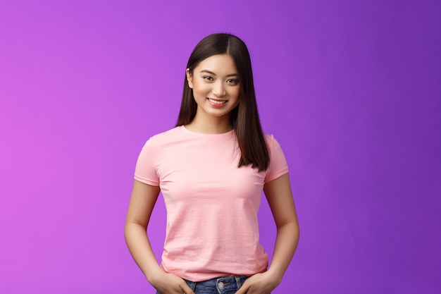 Carino tenera donna asiatica femminile taglio di capelli corto scuro, stare in piedi t-shirt rosa incoraggiata, tenere per mano le tasche dei jeans, sorridere con gioia, mantenere una conversazione interessante, stare in piedi sfondo viola ottimista.