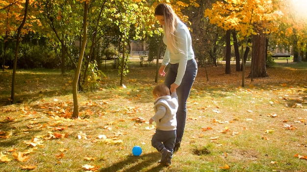 Ragazzo carino bambino che tiene la mano della madre e gioca a calcio nel parco autunnale.