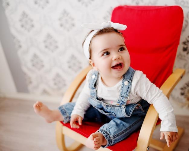 Bambino carino in una sedia, in posa e sorridente. denim da portare della neonata e un panino dei capelli.