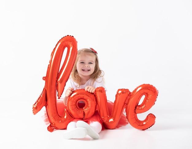 La ragazza sveglia del bambino tiene l'amore dell'iscrizione dai palloncini su una priorità bassa bianca.