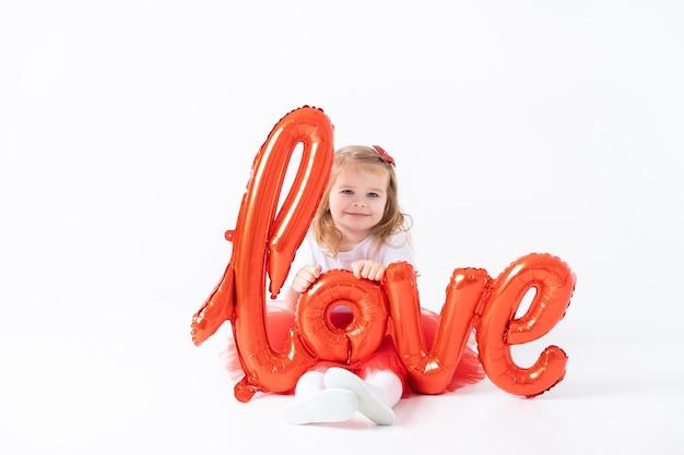 La ragazza sveglia del bambino tiene la scritta amore da palloncini su un muro bianco.