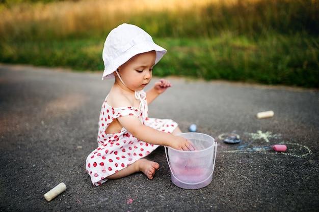 Una ragazza carina all'aperto in campagna, disegno a gesso sulla strada.