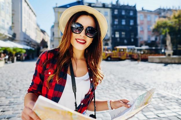 Ragazza carina turistica con capelli castani che indossa cappello, occhiali da sole e camicia rossa, che tiene la mappa al vecchio fondo della città europea e sorridente, viaggiando.