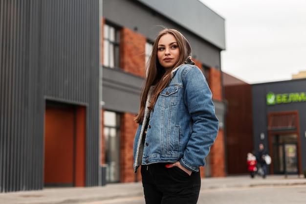 Carina giovane donna americana alla moda in giacca di jeans blu alla moda è in piedi in città vicino all'edificio. bella ragazza urbana che posa in vestiti alla moda sulla via. abbigliamento giovanile americano.