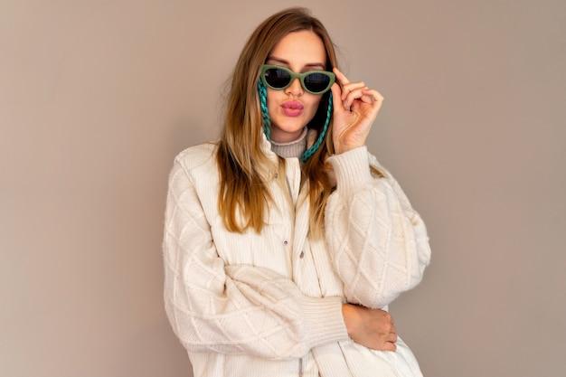Carino ritratto alla moda di una donna bionda alla moda in posa su un muro beige, indossando occhiali da sole luminosi