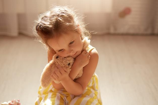 La bambina sveglia di ribaltamento che porta il vestito giallo e bianco si siede sul pavimento con il suo giocattolo molle in mani e lo abbraccia, bambino femminile che si siede sul pavimento.