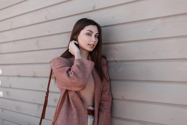 Modello di moda carino giovane donna urbana in elegante abbigliamento primaverile in posa vicino a edificio d'epoca da assi. l'adorabile e bella modella urbana alla moda raddrizza i capelli e si gode il riposo vicino alla parete di legno all'aperto