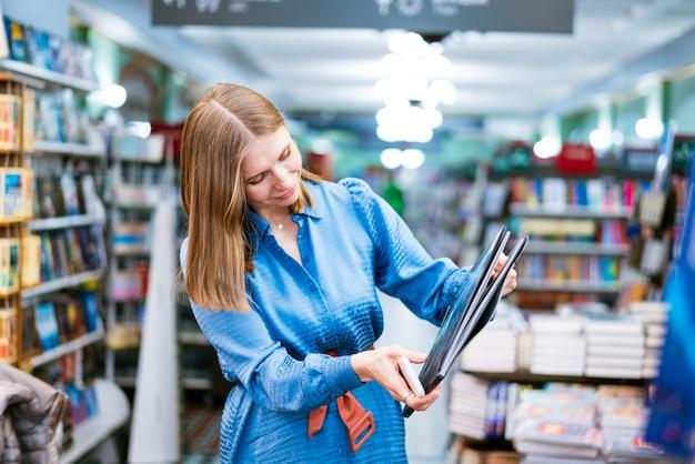 Vista carina di una donna che tiene in mano un libro di carta aperto che legge bestseller da libreria o libreria godendosi...