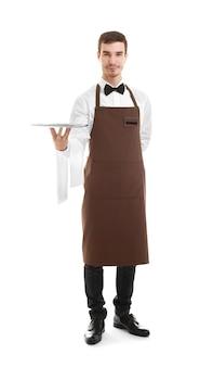 Cameriere sveglio che tiene vassoio e tovagliolo vuoti su bianco