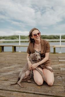 Simpatico cane weimaraner seduto sulle ginocchia del proprietario