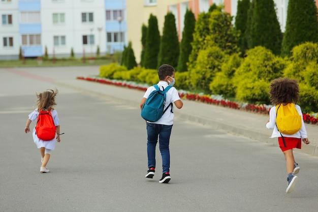 Simpatici studenti bianchi e neri stanno correndo a scuola.