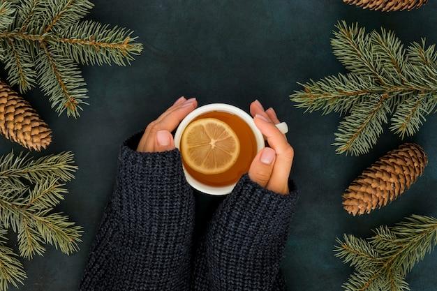 Concetto di inverno carino con donna che tiene tazza di tè