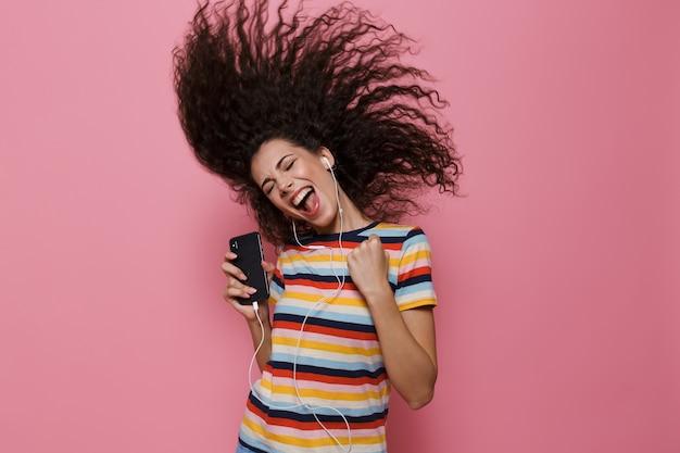 Donna carina 20s con i capelli tremanti che canta mentre tiene in mano lo smartphone e ascolta la musica tramite le cuffie isolate sul rosa