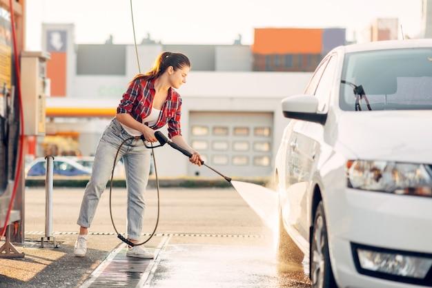 La donna carina pulisce le ruote dell'auto con una pistola ad acqua ad alta pressione.