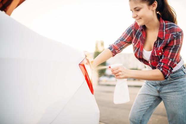 La donna carina pulisce le luci posteriori dell'auto con spugna e spray, autolavaggio. signora sul lavaggio auto self-service. pulizia del veicolo all'aperto in una giornata estiva