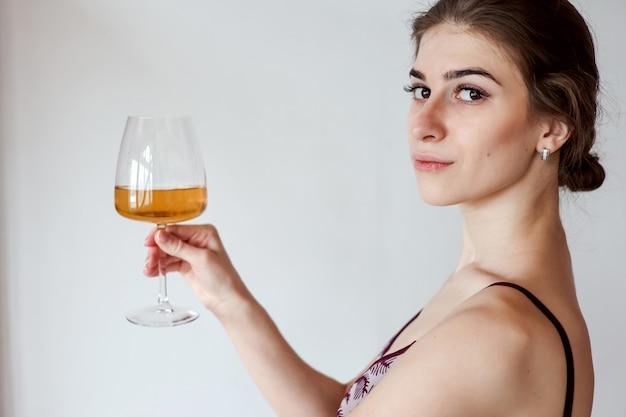 Donna carina che gode del bicchiere di vino bianco. copia spazio, sfondo, spazio negativo per la sovrapposizione di testo, persone reali, elemento umano, estate, toast, bevande, cocktail, celebrazione, applausi, bere