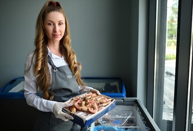Donna carina, pescivendolo al negozio di pesce in piedi con una scatola di enormi gamberoni surgelati, accanto al frigorifero pieno di frutti di mare congelati