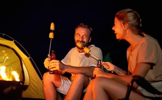 Una donna carina e un bell'uomo sono seduti su sedie pieghevoli vicino alla tenda accanto al fuoco, bevono birra, mangiano mais e si divertono di notte sulla spiaggia in riva al mare.